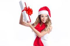 Jeune femme heureuse dans le chapeau de Santa semblant latéral montrant le cadeau de Noël Photographie stock libre de droits