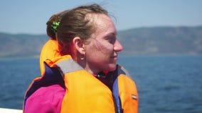 Jeune femme heureuse dans le gilet de sauvetage dans un tour de bateau en bas du lac 3840x2160 clips vidéos
