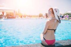 Jeune femme heureuse dans le grand chapeau détendant sur la piscine, voyage près de la plage dans le coucher du soleil été de con Images libres de droits