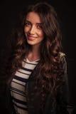 Jeune femme heureuse dans le sourire de veste en cuir Image libre de droits