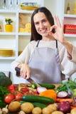 Jeune femme heureuse dans le tablier montrant le geste correct tout en préparante Image stock
