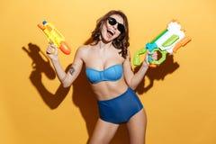 Jeune femme heureuse dans les vêtements de bain tenant l'arme à feu d'eau de jouets Image libre de droits