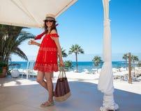 Jeune femme heureuse dans un bain de soleil rouge tenant un sac et un umbrel images libres de droits