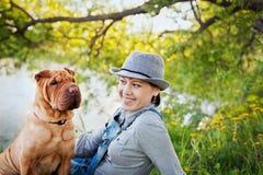 Jeune femme heureuse dans un chapeau avec le chien Shar Pei s'asseyant dans le domaine dans la lumière d'or de coucher du soleil, Photographie stock libre de droits