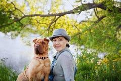Jeune femme heureuse dans un chapeau avec le chien Shar Pei s'asseyant dans le domaine dans la lumière de coucher du soleil, amis Photographie stock