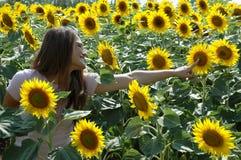 Jeune femme heureuse dans un domaine de tournesol Images stock
