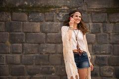 Jeune femme heureuse de boho près de téléphone portable parlant de mur en pierre Photo stock