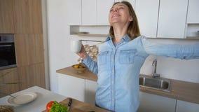 Jeune femme heureuse de commencer nouveau jour avec la tasse de thé dans des mains, se tenant au milieu de la cuisine à la table  banque de vidéos