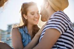 Jeune femme heureuse de couples s'asseyant avec son ami dehors Photo stock