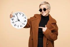 Jeune femme heureuse de hippie avec les cheveux courts blonds utilisant un manteau et un doigt de pinte de lunettes de soleil sur image stock