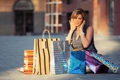 Jeune femme heureuse de mode avec des paniers se reposant sur le trottoir Images stock