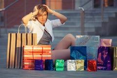 Jeune femme heureuse de mode avec des paniers se reposant sur le trottoir Image libre de droits