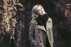 Jeune femme heureuse de mode dans la marche beige classique de manteau extérieure Photographie stock