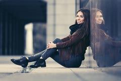 Jeune femme heureuse de mode dans la veste en cuir se reposant au mur sur la rue de ville image stock