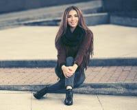 Jeune femme heureuse de mode dans la veste en cuir se reposant sur le trottoir sur la rue de ville images stock