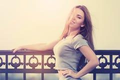Jeune femme heureuse de mode dans le dessus gris de culture et costume de jupe se penchant sur la balustrade photo stock