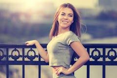 Jeune femme heureuse de mode dans le dessus gris de culture se penchant sur la balustrade photographie stock libre de droits