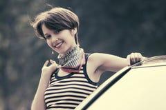 Jeune femme heureuse de mode dans le dessus de réservoir rayé se penchant sur sa voiture Image libre de droits