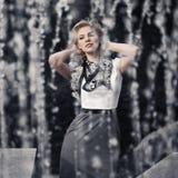 Jeune femme heureuse de mode marchant dans la rue de ville contre une fontaine Photo stock