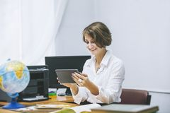 Jeune femme heureuse de professeur dans une salle de classe avec le comprimé électronique photos stock