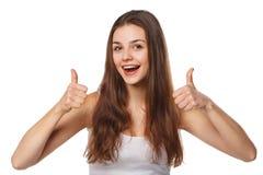 Jeune femme heureuse de sourire montrant des pouces, d'isolement sur le fond blanc photos libres de droits