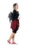 Jeune femme heureuse de style de rue dans les espadrilles et la vue de côté de marche de robe rouge Photo stock