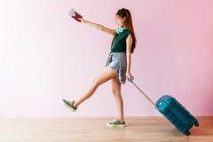 Jeune femme heureuse de voyageur marchant avec la valise et la musique Headp photos stock