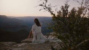 Jeune femme heureuse de vue de dos de mouvement lent avec des cheveux soufflant dans le vent appréciant le paysage épique de couc banque de vidéos