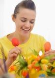 Jeune femme heureuse effectuant la décoration de Pâques avec le TU Photographie stock libre de droits