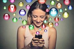 Jeune femme heureuse employant le service de mini-messages sur le smartphone Image stock
