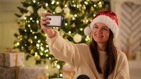 Jeune femme heureuse en Santa Hat Doing Selfie par Smartphone pendant la célébration de Noël Jolie photographie de fille banque de vidéos
