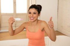 Jeune femme heureuse et enthousiaste tenant un essai de grossesse regardant le résultat positif dans la joie Photos libres de droits