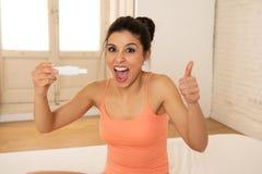 Jeune femme heureuse et enthousiaste tenant un essai de grossesse regardant le résultat positif dans la joie Photographie stock libre de droits