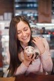 Jeune femme heureuse et son furet d'animal familier Photographie stock