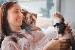 Jeune femme heureuse et son furet d'animal familier en café Images stock