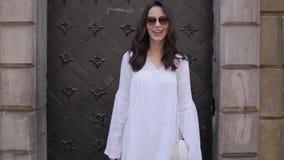 Jeune femme heureuse et souriante à la mode posant dans la rue de ville banque de vidéos