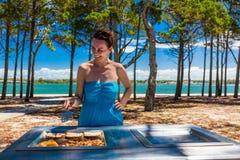 Jeune femme heureuse faisant cuire le barbecue sur la plage dans l'Australie Photo libre de droits