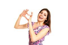 Jeune femme heureuse faisant le coeur d'amour avec ses mains sur un Ba blanc Images stock