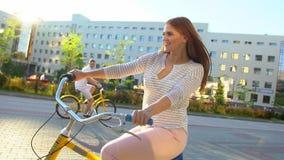 Jeune femme heureuse faisant un cycle heureusement par une rue ensoleillée dans l'été dehors Bicyclette d'équitation de fille de  clips vidéos