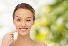 Jeune femme heureuse indiquant le doigt son sourire image stock