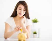 Jeune femme heureuse insérant la pièce de monnaie à la tirelire Photographie stock