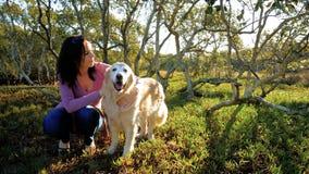 Jeune femme heureuse jouant avec le chien de golden retriever en parc banque de vidéos