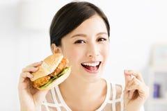 Jeune femme heureuse mangeant le grand hamburger Images libres de droits