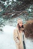 jeune femme heureuse marchant sous les pins dans la forêt neigeuse d'hiver photographie stock libre de droits