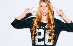 Jeune femme heureuse montrant deux mains Victory Sign et montrant la langue sur le fond blanc Fin vers le haut d'intérieur Couleu Photographie stock