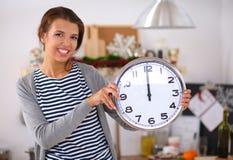 Jeune femme heureuse montrant l'horloge dans Noël Images libres de droits