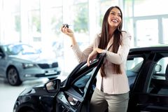 Jeune femme heureuse montrant la clé de la nouvelle voiture photographie stock