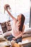 Jeune femme heureuse montrant son furet d'animal familier en café Photographie stock