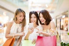 Jeune femme heureuse observant le téléphone intelligent dans le centre commercial Images libres de droits