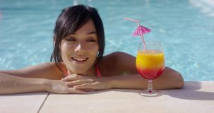 Jeune femme heureuse observant un grand cocktail tropical clips vidéos